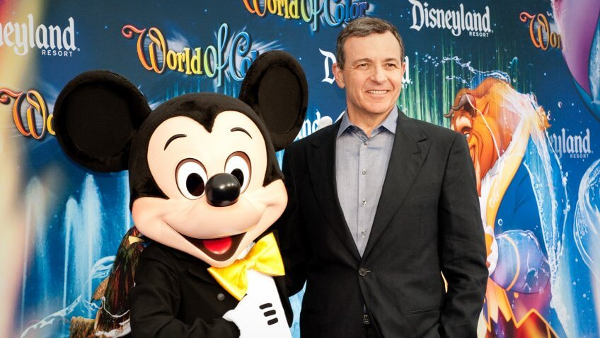 Bob Iger poses for a picture with a person in costume as Mickey Mouse