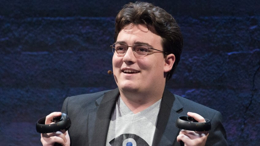 Palmer Luckey (Founder, Oculus) holding up to chest Oculus Touch prototype Half Moon at Step into the Rift.