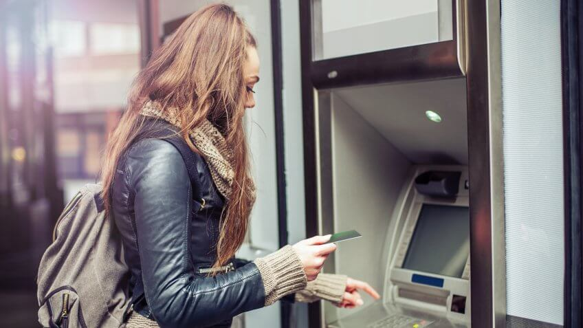 Young woman withdrawing money from credit card at ATM,, fees, America, money, payment, avoid fees, bills, debt