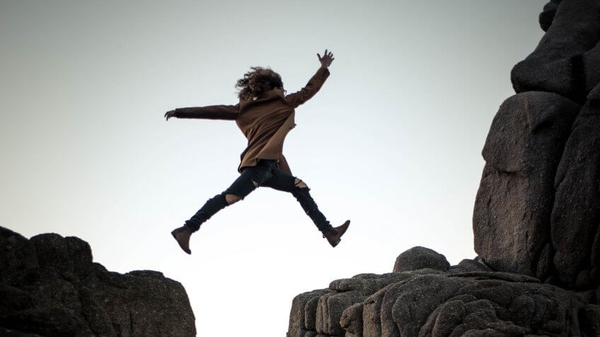 Woman taking a risk by jumping between two cliffs