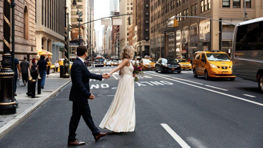 Bride holds groom's hand walking across the street in New York.