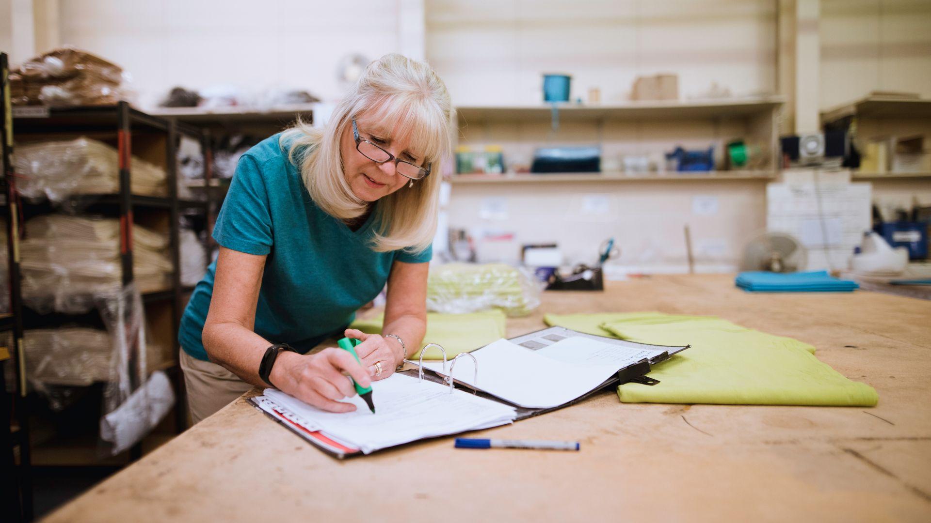 Senior businesswoman is doing paperwork in her stock factory