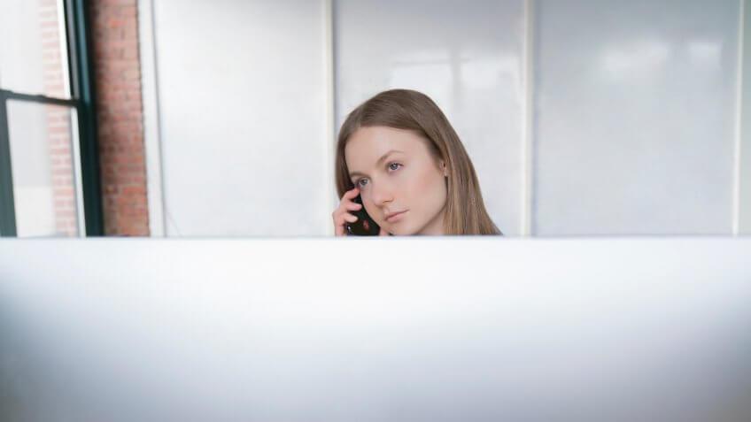 Young woman bored at a job taking a phone call