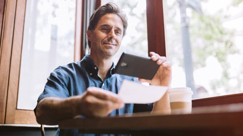 "A mature smiling man in his mid 40's takes a picture with his smart phone of a check or paycheck for digital electronic depositing, also known as ""Remote Deposit Capture"", fees, America, money, payment, avoid fees, bills, debt"
