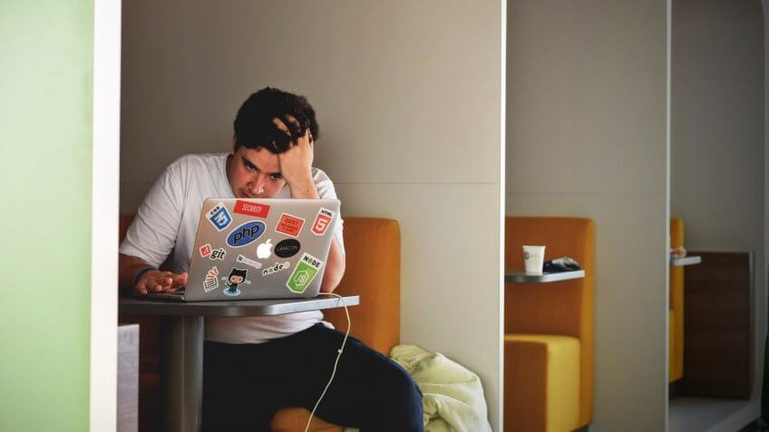 Young man stressed about work on laptop