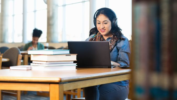 Stock, shares, NASDAQ, S&P 500, money, Young adult Hispanic woman is studying in college library.
