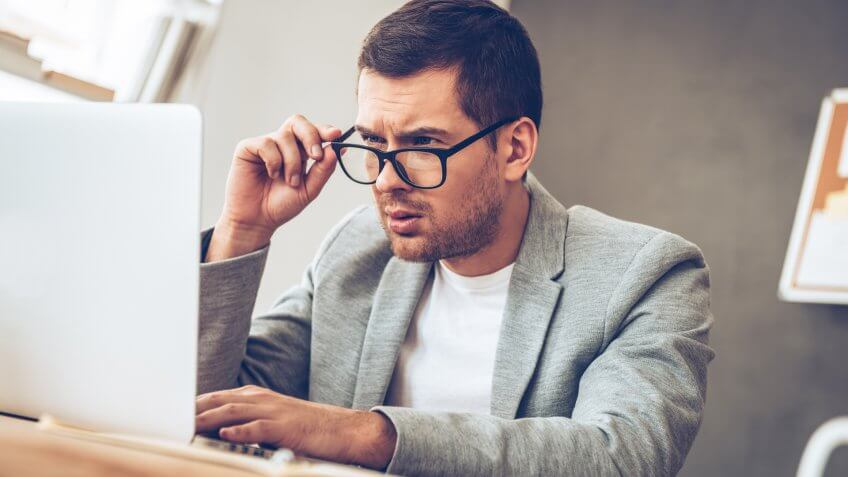 Handsome young man looking at his laptop and adjusting his glasses while sitting at his working place, fees, America, money, payment, avoid fees, bills, debt