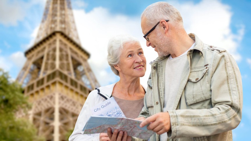 Senior couple on vacation navigating Paris with Eiffel Tower in the background