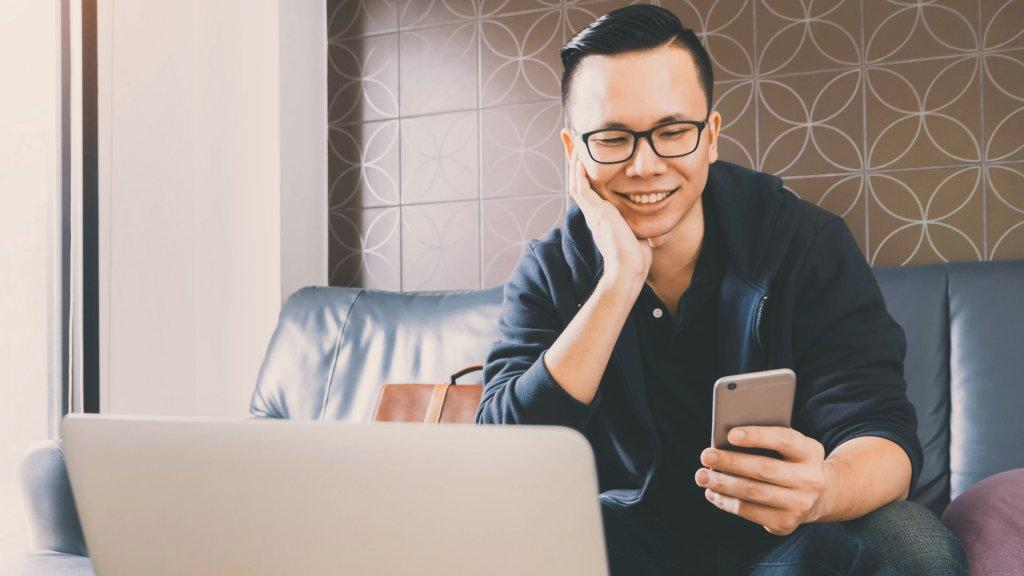 Stock, shares, NASDAQ, S&P 500, money, Happy asian businessman using smartphone while sitting on sofa at home office background with vintage filter.
