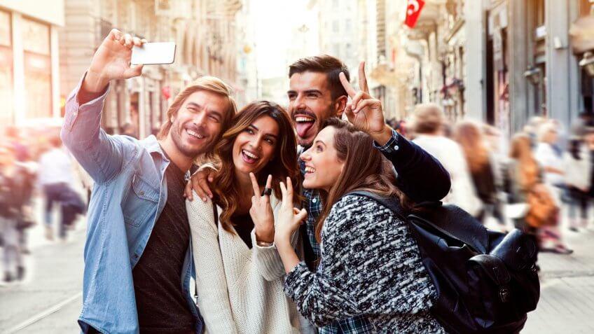 Happy friends taking a selfie in the city