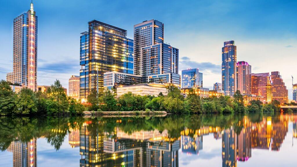 Stock photo of the skyline of downtown Austin, Texas, USA with apartment buildings and office buildings, reflecting in the Colorado River during the dawn twilight blue hour.