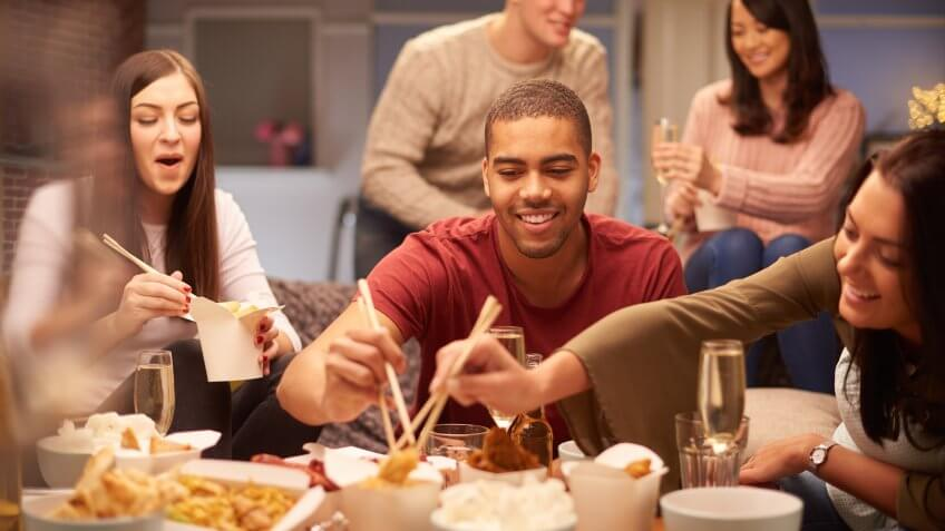 Stock, shares, NASDAQ, S&P 500, money, a group of young friends sit on the sofa and share a chinese take away meal , chatting and laughing with each other as they use their chopsticks to eat .
