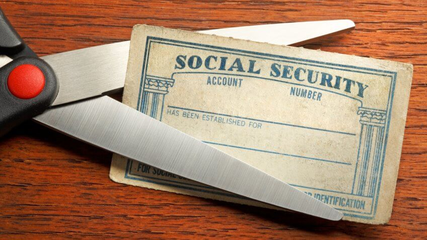 A pair of scissors about to cut a blank Social Security card that sits on a desk top.