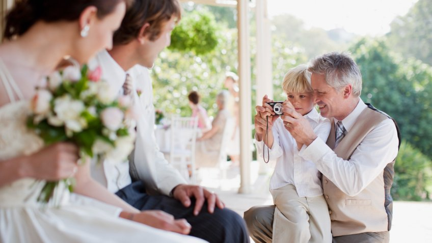 Father and son taking picture of bride and groom.