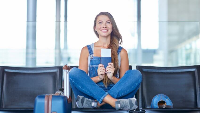 Shot of a young woman holding her passport and ticket while sitting on a chair in an airport departure lounge