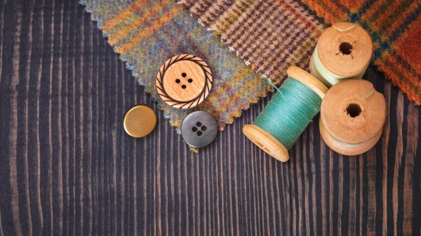 Stock, shares, NASDAQ, S&P 500, money, Thimble, buttons, spools of thread and fabric swatches on a wooden background close up.