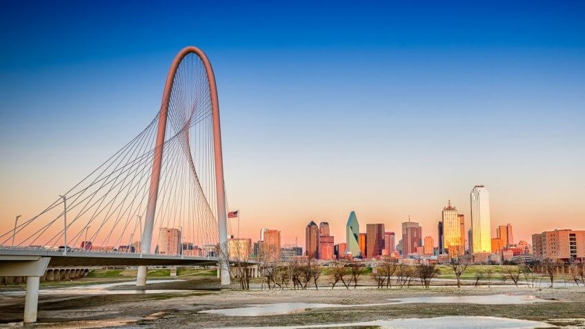 Dallas skyline from the west near sunset on the banks of the trinity river seen from the Margaret Hunt Hill bridge on the left to Reunion Tower on the right.