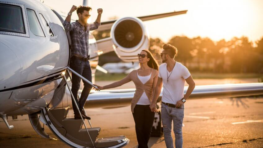 Young casual people with sunglasses standing in front of private jet airplane