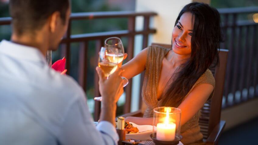 Stock, shares, NASDAQ, S&P 500, money, Couple having intimate dinner for two on the terrace of summer evening.