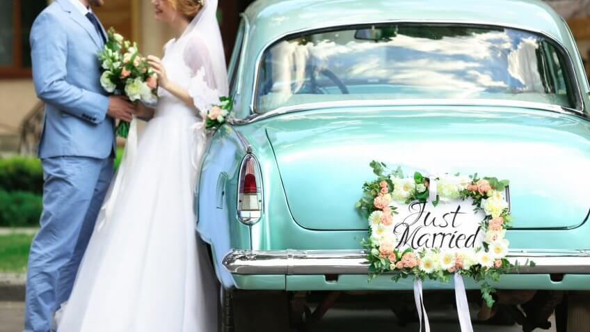Happy wedding couple near decorated car, outdoors.