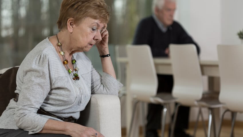 Upset elderly woman sitting on couch with husband in background