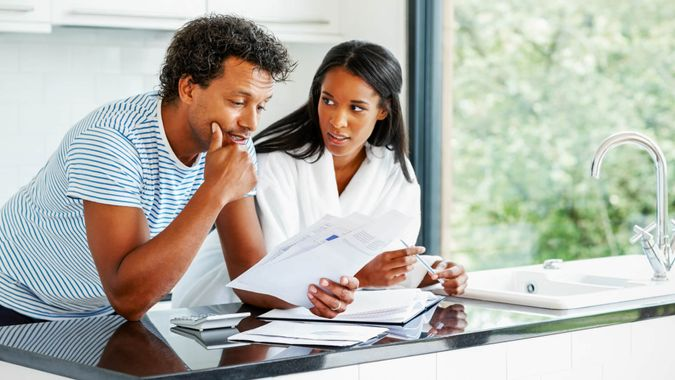 Portrait of worried young couple reading financial documents in kitchen, fees, America, money, payment, avoid fees, bills, debt