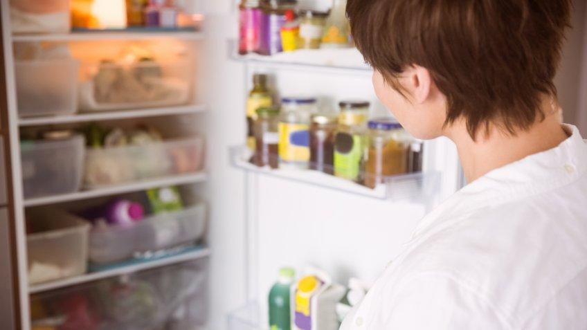 Woman looking into refrigerator