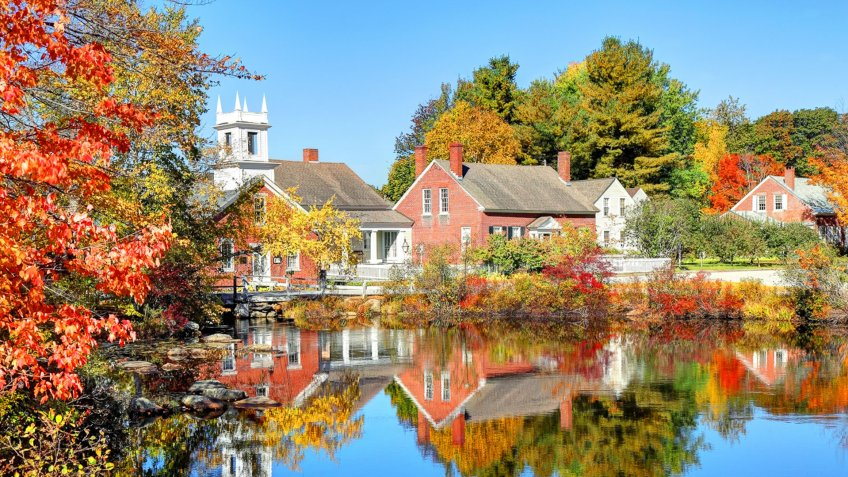 The quaint village of Harrisville New Hampshire reflecting on a small pond in autumn.