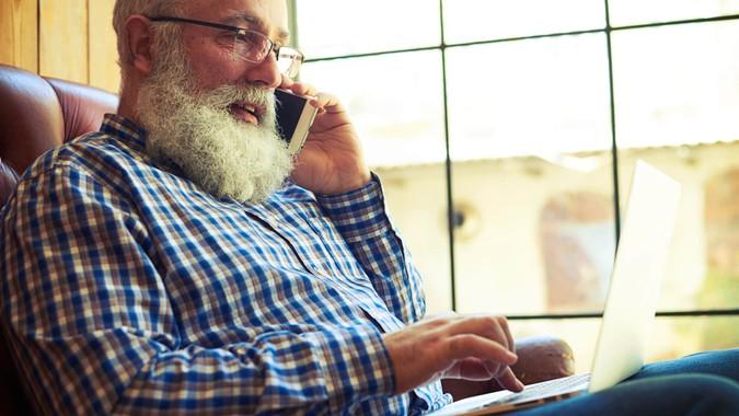 Senior man making a phone call while using laptop