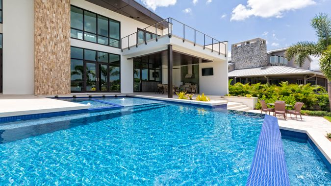 A beautiful modern swimming pool and home on a sunny day with outdoor living area