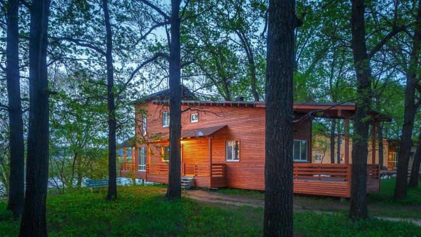 minimalistic wooden house in oak forest in summer