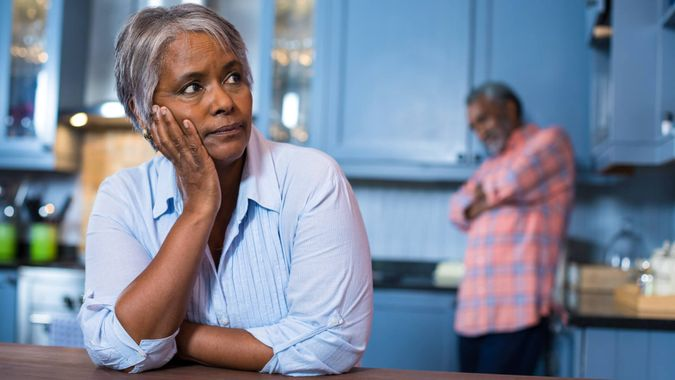 Thoughtful woman with man in background at home.