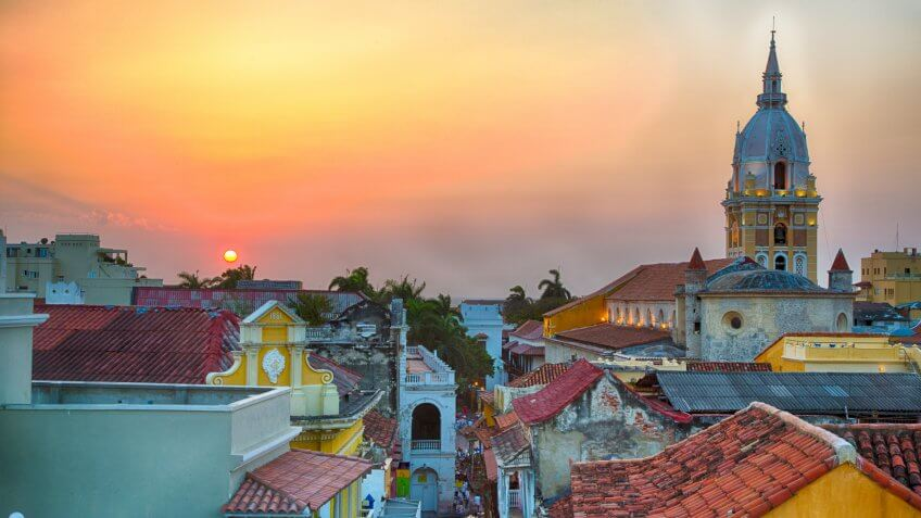 View over the rooftops of the old city of Cartagena during a vibrant sunset.