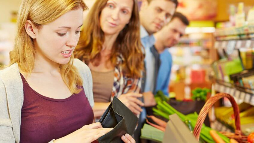 Woman in line at grocery market looks into an empty wallet