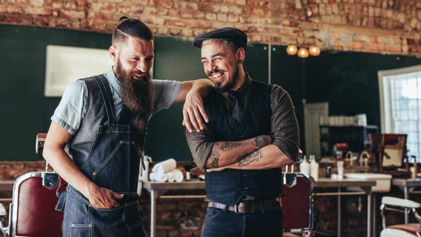 Shot of hairdresser with a man standing at barbershop.