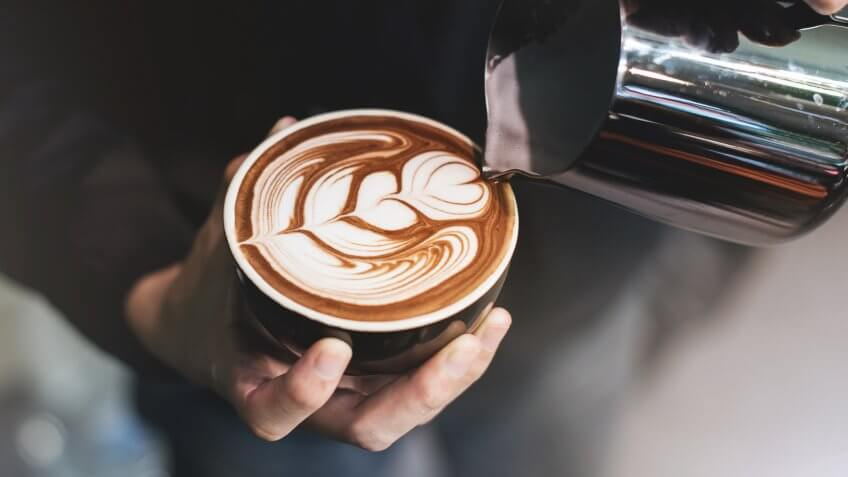 Barista make coffee cup latte art.