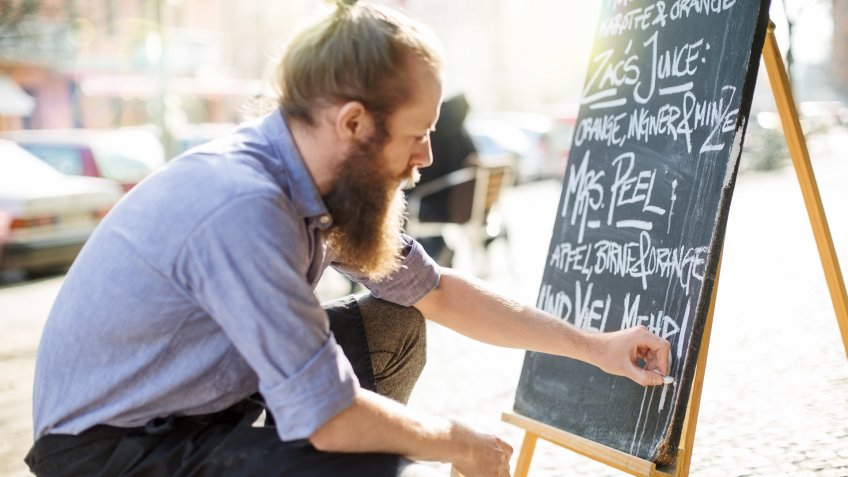 Waiter writing todays special on the board outside the cafe.