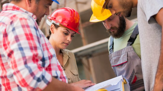 Three workers gathered in a circle around an architect holding blueprints