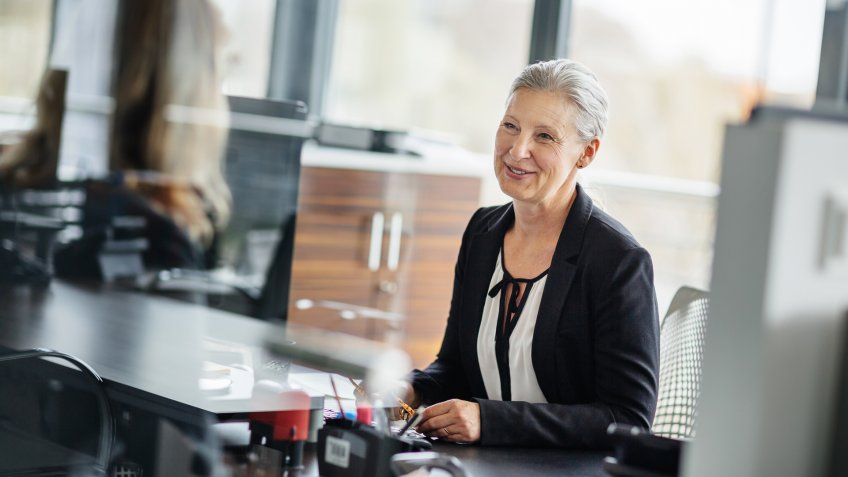 Senior businesswoman sitting on her desk in a modern office and talking with an employee.