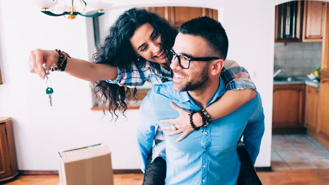 Young couple holding the keys for their new home