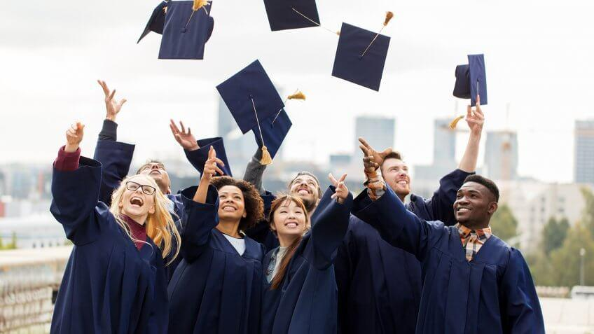 education, graduation and people concept - group of happy international students in bachelor gowns throwing mortar boards up in the air.