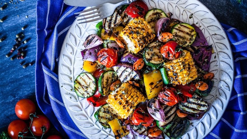 Grilled vegetables plate shot from above on bluish kitchen table.