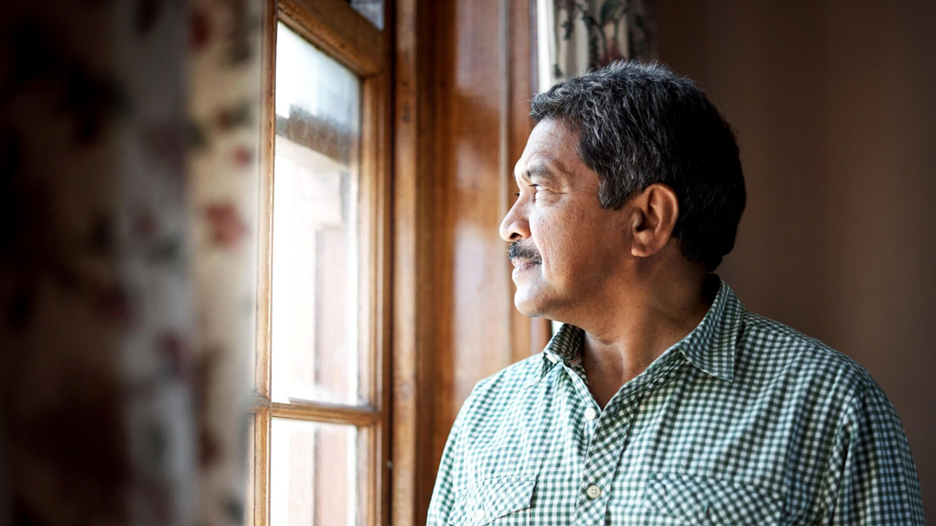 Senior man looking out the window at home