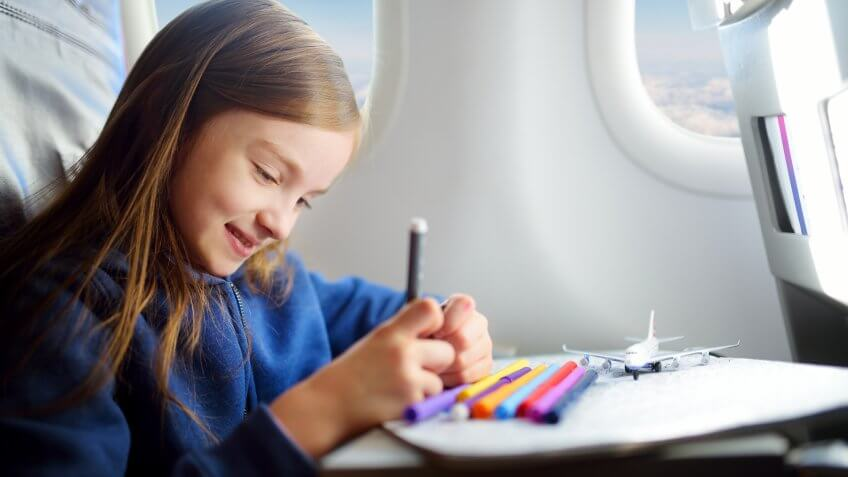 kid drawing in airplane seat