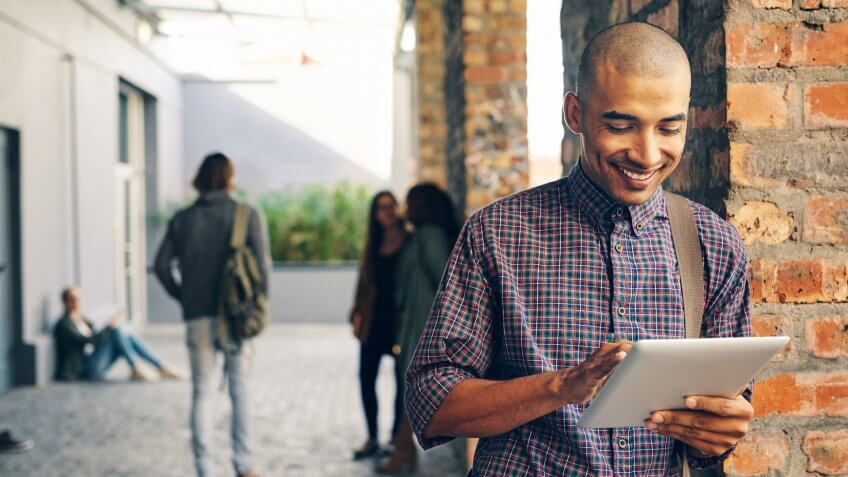 Shot of a young man using a digital tablet outdoors on campus.