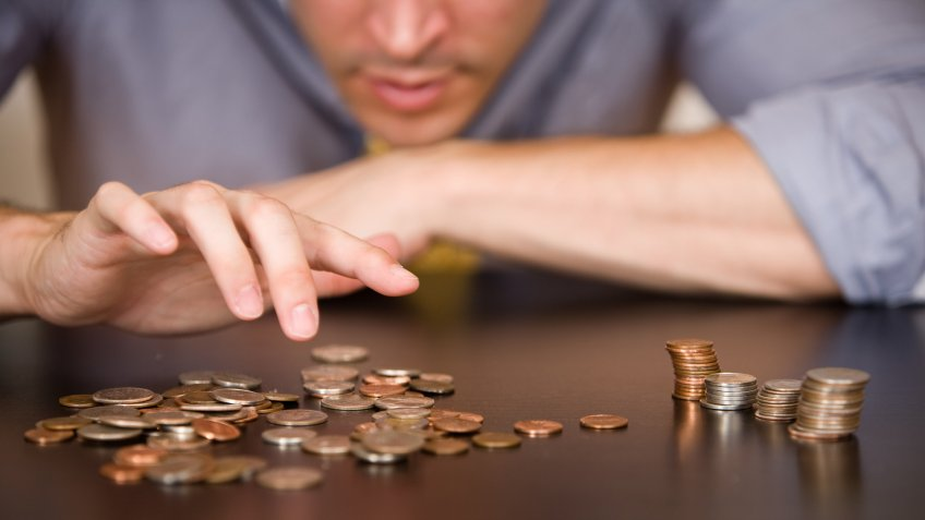 A man counts his coins on a tabletop.