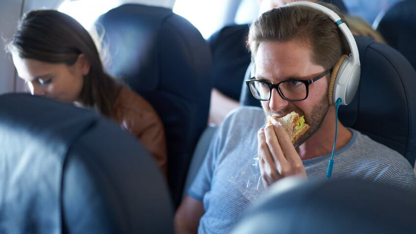 Man eating sandwich in economy class in airplane.