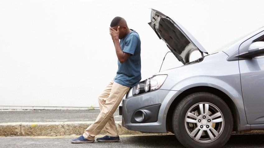 man with broken down car