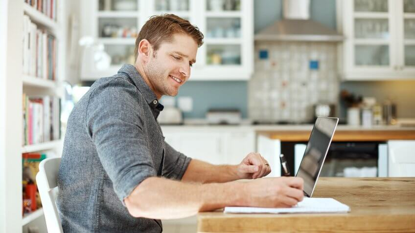 Shot of a young man using a laptop and writing notes at home.