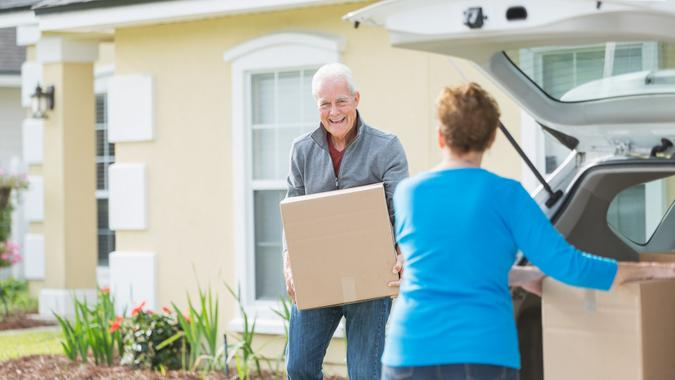 A senior couple lifting cardboard boxes into or out of the back of a car